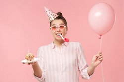 Young happy birthday girl wearing colored glasses and holiday hat, holding balloon, cake and whistle in mouth, isolated on pink background