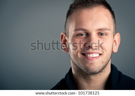 Young happy boy close up portrait against grey background with room for text.