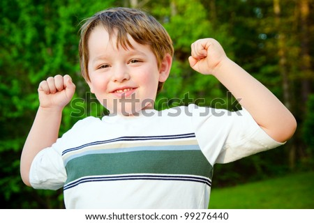 Young happy boy or kid cheering outdoors