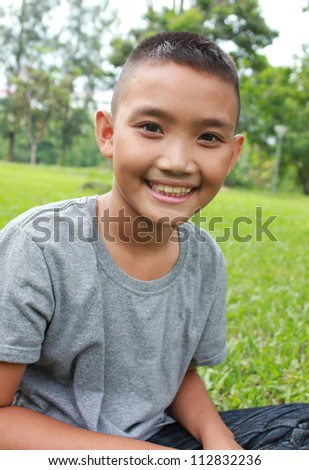 Young happy boy sitting in the park.
