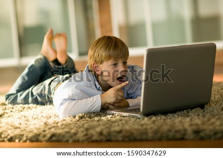 Young happy boy using laptop