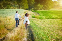 Young happy bride and groom ride bicycles in the meadow back to camera and holding hands.