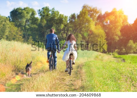 Young happy bride and groom ride bicycles in the meadow back to camera and holding hands. #204609868