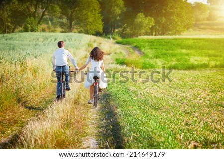 Young happy bride and groom ride bicycles in the meadow back to camera and holding hands. #214649179