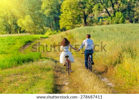 Young happy bride and groom ride bicycles in the meadow back to camera and holding hands