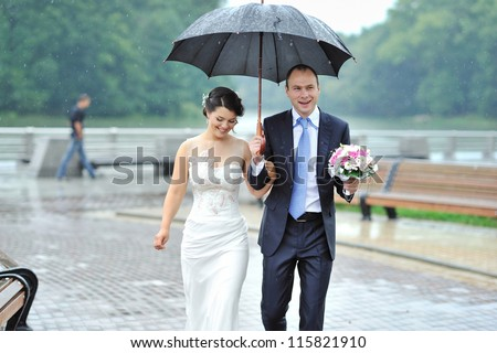 Young happy bride and groom walking by the rain