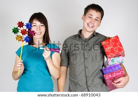 young happy brunette man and girl holding many gifts and other party items and smiling