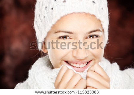 young happy brunette woman in wool sweater and cap, isolated on white