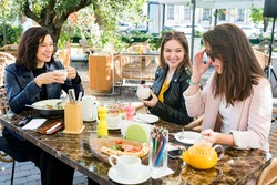 Young happy brunette women friends in casual clothes having fun and laughing during brunch in cafe outside on sunny day. Selective focus