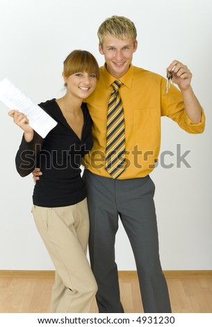 Young, happy business couple. Man is holding keys, woman is holding  some kind of contract. Looking at camera, front view