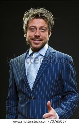Young happy business man holds thumb up in blue striped suit. Black background. Studio portrait. Luck. Gesture. Good. Relaxed.