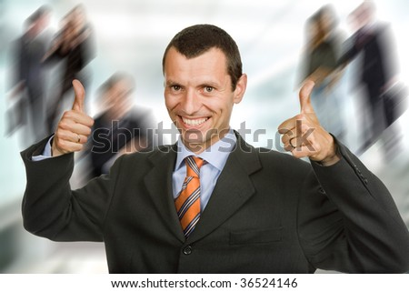 Young happy business man showing thumbs up