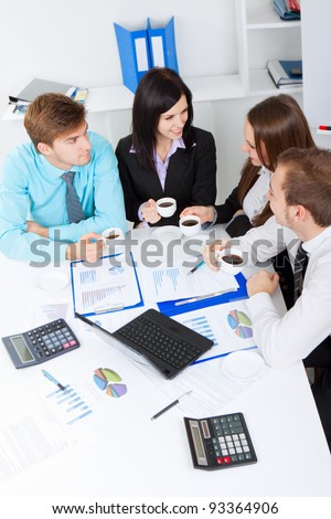 Young happy business people, drinking coffee and talking, break, smiling, working on project in team together, men and women discussing, businesspeople meeting sitting at desk office, above top view