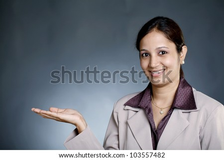 Young happy business  woman holding her hand palm up