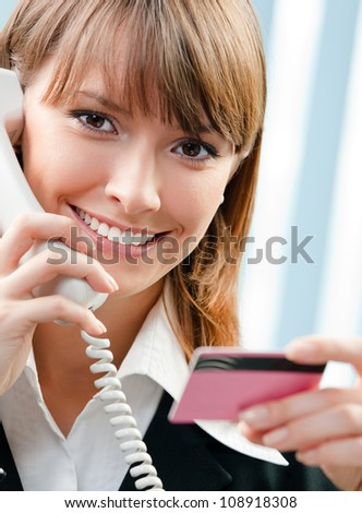 Young happy business woman with phone and credit card, at office