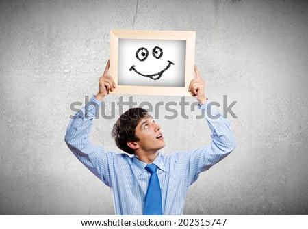 Young happy businessman holding frame with drawn smile