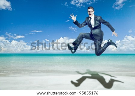 Young happy businessman jumps in black suit on tropical beach.