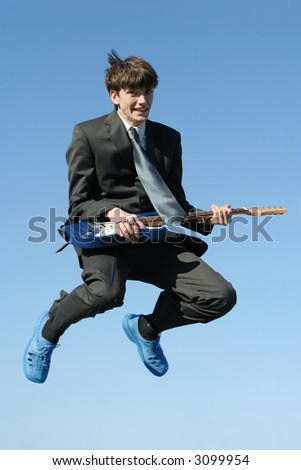 young happy businessman with guitar jumping high