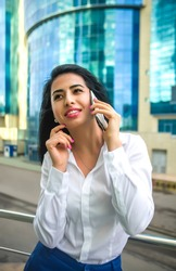 Young happy businesswoman speaking on cellphone over city background. asian  business woman dreaming and looking  at far away. skyscraper - modern business building - on background. welldressed female
