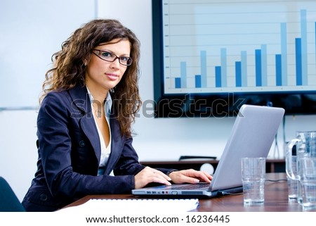 Young happy businesswoman working on laptop computer in meeting room at office, looking at camera smiling.