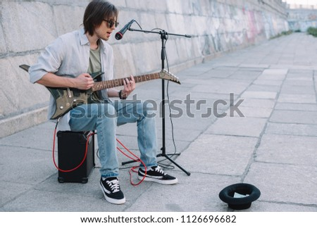 Young happy busker playing guitar and singing at city street