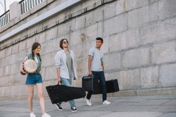 Young happy buskers walking and carrying musical instruments at city street