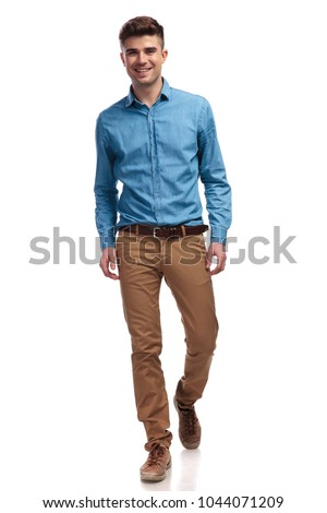 young happy casual man walking forward to the camera on white backround #1044071209