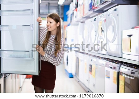 Young happy cheerful  woman choosing new refrigerator in household appliances shop