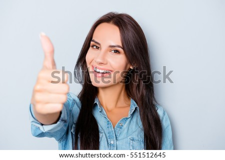 Young happy cheerful woman showing thumb up