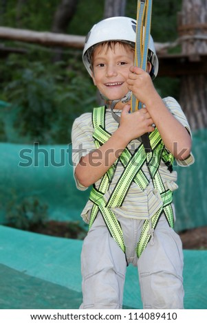 young happy child boy in adventure park wearing mountain helmet and safety equipment