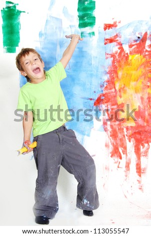 young happy child boy painting white wall with colours