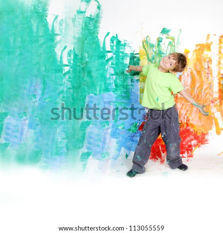 young happy child boy painting white wall with colours - stock photo