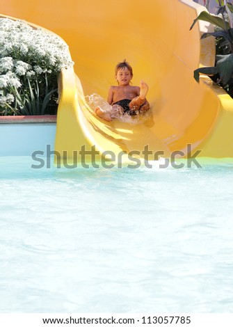 young happy child boy riding slides in aqua park