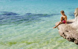 young happy child boy sitting on rocks on tropical sea background