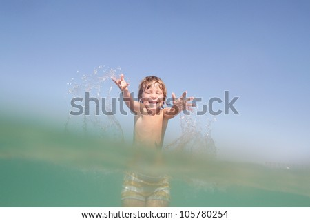 young happy child having fun in water