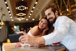 Young happy couple at a date making selfie in a coffee shop