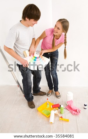 Young happy couple choosing color in palette in new house