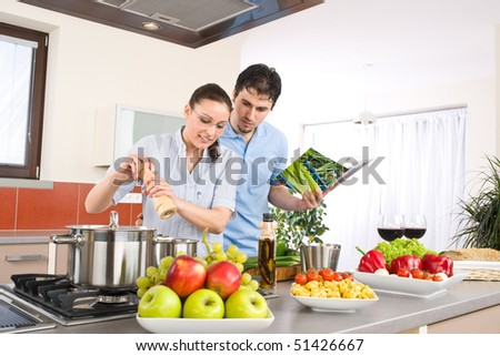 Young happy couple cook in kitchen with cookbook, pasta, vegetable