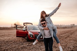 Young Happy Couple Dressed Alike in White Shirt and Jeans Enjoying Road Trip at Their New Car, Beautiful Sunset on the Field, Vacation and Travel Concept