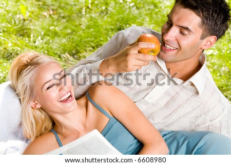 Young happy couple eating apples and reading newspaper outdoors
