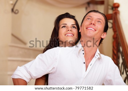 Young happy couple embracing in an new house and looking up