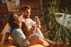 Young happy couple enjoy in beer by the river during the sunset