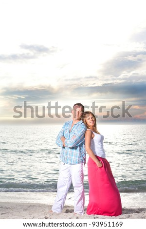 Young happy couple enjoy summer day at a beach.