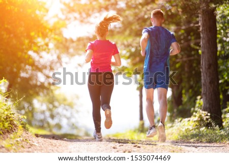 young happy couple enjoying in a healthy lifestyle while jogging on a country road through the beautiful sunny forest, exercise and fitness concept #1535074469