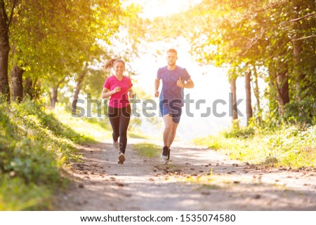 young happy couple enjoying in a healthy lifestyle while jogging on a country road through the beautiful sunny forest, exercise and fitness concept #1535074580