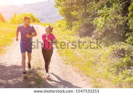 young happy couple enjoying in a healthy lifestyle while jogging on a country road through the beautiful sunny forest, exercise and fitness concept #1547533253