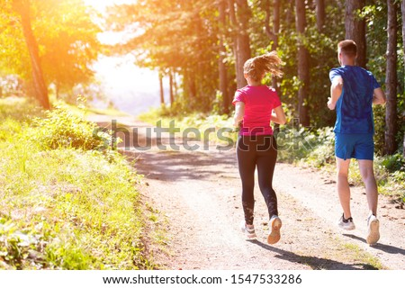 young happy couple enjoying in a healthy lifestyle while jogging on a country road through the beautiful sunny forest, exercise and fitness concept #1547533286