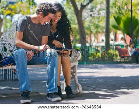 Young happy couple enjoying looking at an electronic pad - stock photo