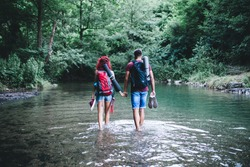 Young happy couple enjoying together in wild mountain river.