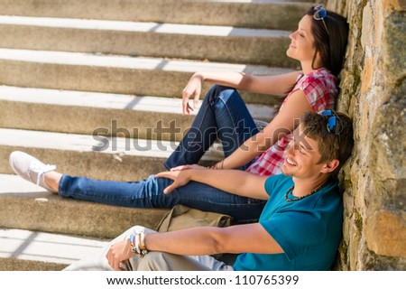 Young happy couple flirting on the stairs smiling romance relaxing - stock photo